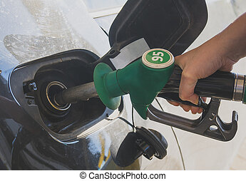 Female hand refueling car at gas station.