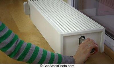 Female hand senses the temperature of the battery. radiator...