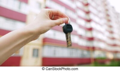 Female hand shakes the keys from a new apartment.