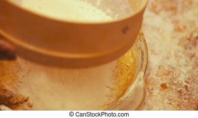 Female hand sifted flour through a sieve