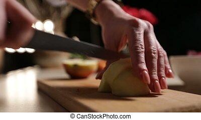 Female hand slicing peeled apple on cutting board