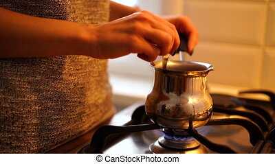 Female hand steering coffee in cezve over gas stove at...