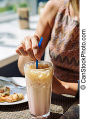 Female hand stirring cold drink in glass with straw