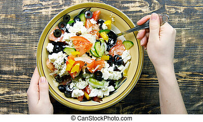 Female hand stirring fresh vegetable salad with cheese feta in the kitchen . The mixing of vegetables. Close-up
