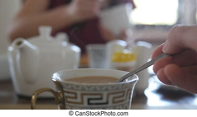 Female hand stirring sugar or milk in a cup of hot coffee or...