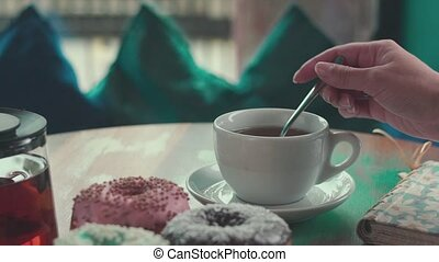 Female hand stirs sugar in a cup of tea. Morning breakfast. Appetite.