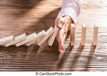 Female Hand Stopping The Domino From Falling