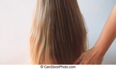 Female hand stroking a girls hair. Cute girl with long blond...