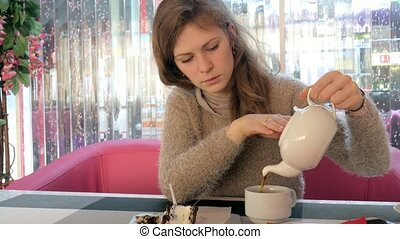 female hand stroking the cup of tea in cafe. Woman in...