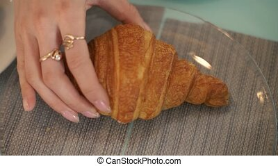 Female hand taking croissant from glass plate at table in...