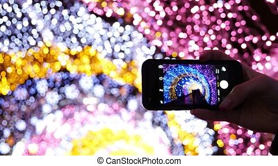 Female hand taking photos of light decoration with their cell phone