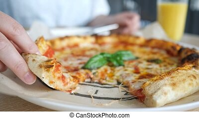 Female hand taking pizza slice. Hot melted cheese is stretching, close-up. Fast-food concept.