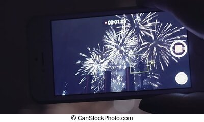Female hand taking video to fireworks on smartphone. Close up