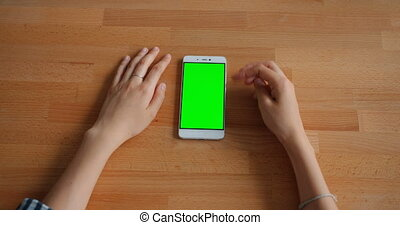Female hand touching green mock-up smartphone screen lying...