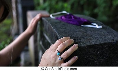 Selective focus of young woman hand touching tombstone at cemetery mourning for deceased during covid-19 pandemic outbreak with mask lying on stone