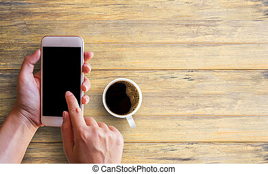 Female hand using smartphone white screen and cup of coffee on wood table in office desk.