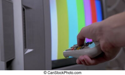 Female Hand Using TV Remote Control Tries a Switch SMPTE Color Bars Test Pattern. Strong finger pressing on buttons. No signal, technical problems, vertical color bars on an old vintage TV. 4K.