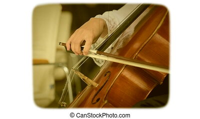 Female hand with a bow plays on a double bass. 8mm retro...