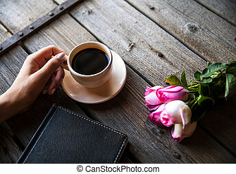 Female hand with a cup of coffee, book and flowers on wooden background. Flowers, break, work