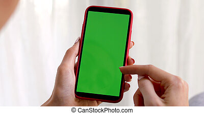Female hand with a green screen smartphone