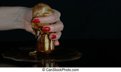 Female hand with a red manicure sexually squeezes a waffle cup with melting ice cream