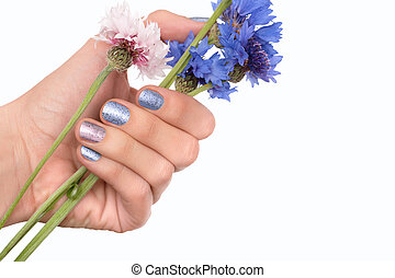 Female hand with blue nail design holding blue flowers.