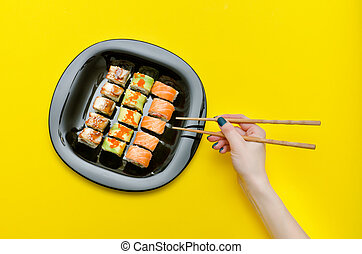 Female hand with chopsticks and plate with various rolls. Yellow background. Top view