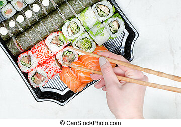 Female hand with chopsticks and sushi set. Yellow background. Top view