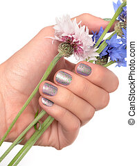 Female hand with glitter nail design holding blue and pink flowers.