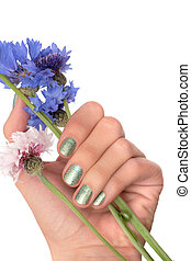 Female hand with green nail design holding blue flowers.