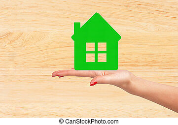 Female hand with model of house on wooden table background