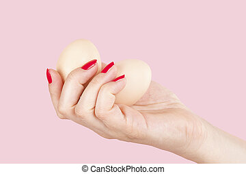 Female hand with red fingernails holding two eggs. - Female...
