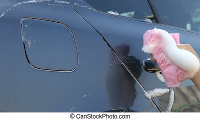 Female hand with red rag washes the car with foam