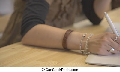 Female hand with rings draws using a graphics tablet sitting at table.