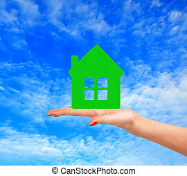 Female hand with small model of house over blue sky