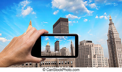 Female hand with smartphone taking a picture of New York skyline
