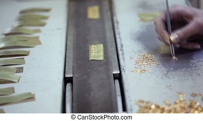Female hand with tweezers, gold items on conveyer belt