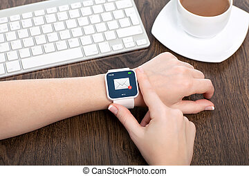 female hand with white smartwatch with email on the screen over a wooden table in an office