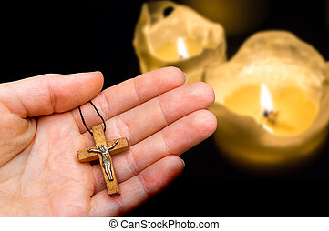 Female hand with wooden cross on candles background
