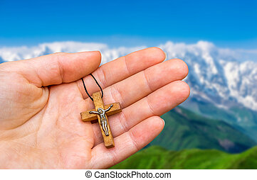 Female hand with wooden cross on mountains background
