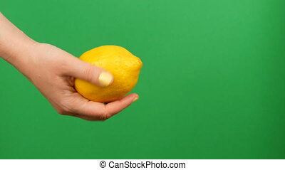 Female hand with yellow manicure holds a lemon on green chroma key background