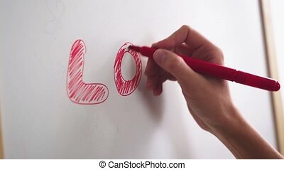 Female hand writes the word LOVE with a marker on a white board.