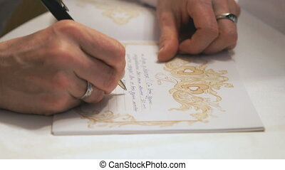 Female hand writing greeting text in book.Close up