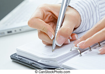 Female hand writing notes