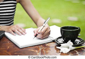 Female hand writing. - Female hand writing and a cup of...