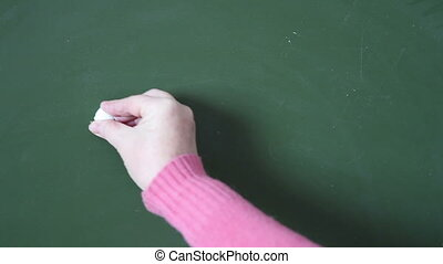 female hand writing with chalk on a blackboard