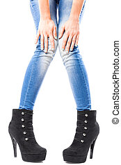 female hands and legs in jeans and high heels