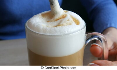 Female hands are stirring the air froth from the latte with...