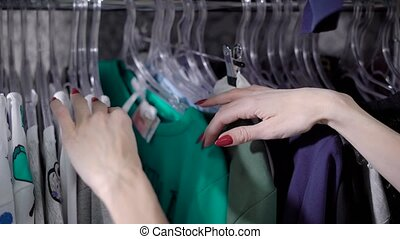 female hands are touching, plucking and moving hangers with...
