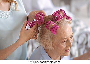 Female hands attaching pink hair rollers